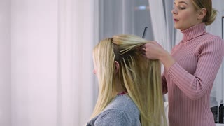 young woman hairdresser makes hairstyle on the bride's wedding