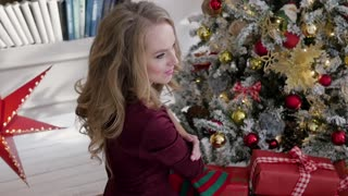 young woman sitting with gifts on the background of a christmas interior. Home Christmas Internet