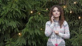 young woman talking on the phone on the background of a Christmas tree and lights.