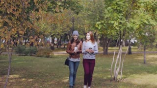 young women walking in the Park and drink coffee