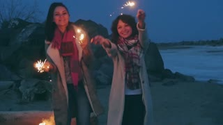 young women with sparklers against the night shore