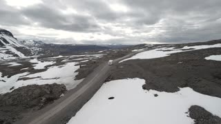 Aerial of an RV Camper Driving Along an Empty, Snowy Road