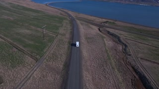 Aerial of an RV Camper Driving Along and Empty River Road Bridge