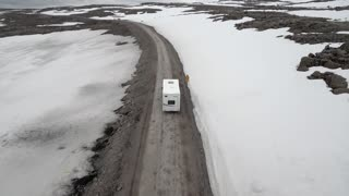Close Up Aerial of an RV Camper Driving Along an Empty, Snowy Road