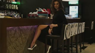 A beautiful girl is sitting at the bar counter