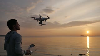 A man controls a drone at sunset