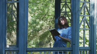 Asian girl reading book in gazebo