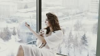 Beautiful Girl Drinking Tea or Coffee at home. Woman enjoying and looking out the window on the city.