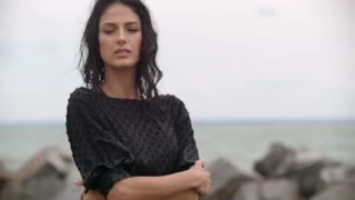 Close up portrait of beautiful girl serious sensual wet hair blowing in wind in rainy weather slow motion