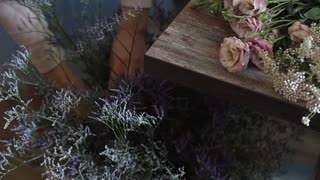 Florist prepares a bouquet of flowers for sale to customers in love. Floral design, floral arts, creating flower arrangements from cut flowers, foliages, herbs, ornamental grasses, plant materials.