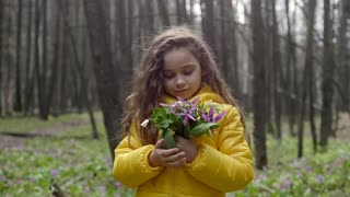 Girl with a bouquet of forest flowers
