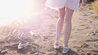 Legs of beauty girl walking barefoot along wet sand beach over sunset. Bare feet of young woman walking on beach beside ocean. Slowmotion video footage. Full HD 1920x1080p.