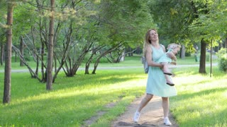 Mother and Baby having fun Outdoors. Together in Green Summer Park. Mom and Child. Happy Family Smiling. Beautiful family in spring park enjoying nature. Slow motion