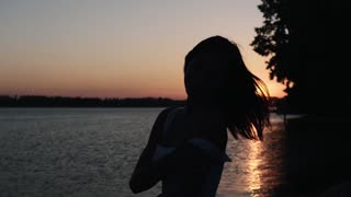 Portrait of a girl at sunset. Silhouette of a girl from the back.