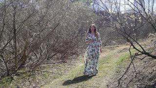 Pregnant woman standing on the river bank, slow motion