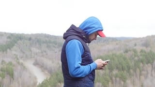 Strong man hiker taking photo with smart phone at mountain peak