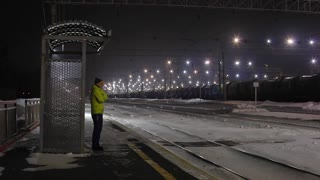 Train station master checks train and waves to driver to clear departure.