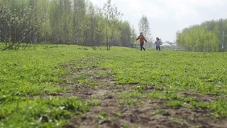 two kids,a boy and a girl running around in the garden holding hands and laughing ,slow motion