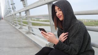 Woman using smartphone in the European city. Slow Motion, 4K. Hipster girl browsing Internet on a phone, texting and communicating outdoors. Travel.