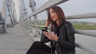 Woman using smartphone in the European city. Slow Motion. Hipster girl browsing Internet on a phone, texting and communicating outdoors. Travel.