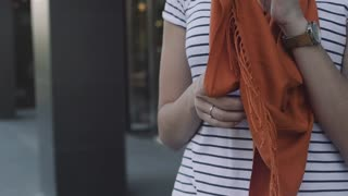 Women's hands touch the scarf