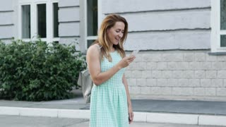 Young happy teenager talking on cellphone in the city 4K