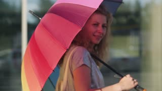 Young woman in beautiful dress with shopping bags and with a bright umbrella goes on the street through the sun during sunset in slowmotion