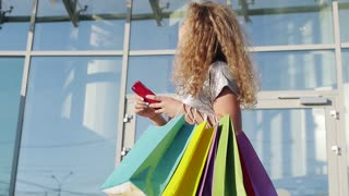 Young woman in beautiful dress with shopping bags and with a smartphone goes on the street through the sun during sunset in slowmotion
