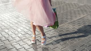 Young woman in beautiful dress with shopping bags goes on the street through the sun during sunset in slowmotion