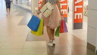 Young woman in beautiful dress with shopping bags goes shopping slowmotion