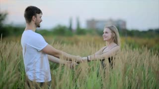 A loving couple.  Guy kisses a woman and then jokingly drops her. Fun young man and woman holding hands and whirling in the field and girl falls to the ground. Slow motion