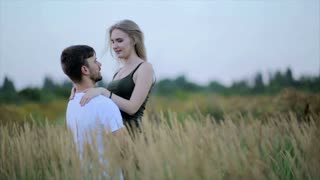A loving couple.  Guy kisses a woman and then jokingly drops her. Fun young man and woman holding hands and whirling in the field and girl falls to the ground