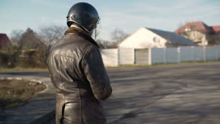 A young man goes to his motorcycle, sits on it and puts a helmet to go on a journey
