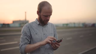 A young man uses his smart phone in the street at sunset or sunrise