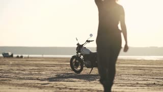 Attractive beautiful woman goes to her old cafe racer motorcycle, sits on it and rides away. Female motorcycle rider.