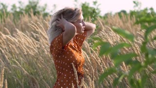 attractive fun hippie blonde woman in the field at sunset having good time outdoors. Slow motion. Female spinning in the field