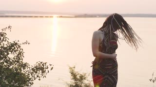 attractive hippie woman with dreadlocks at sunset having good time and dance outdoors
