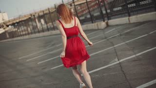 Attractive young red-haired woman running on street in red dress, having a good time at sunset. Slow motion
