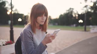 attractive young red-haired woman uses smatphone in park at sunset