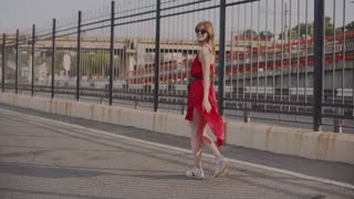 Attractive young red-haired woman walking on street in red dress, having a good time at sunset. Slow motion