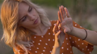 Attractive young woman hands with golden glitters in the field on sunset. Slow motion