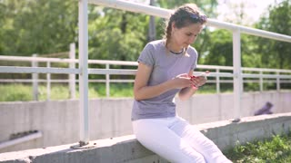 attractive young woman uses smatphone in park at day