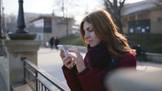 Beautiful woman using smart phone technology app in city streets at cold sunny day