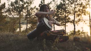 Beautiful young hippie woman with dreadlocks playing on djembe. Funky woman drumming in nature on an ethnic drum at sunset or sunrise with a human skull