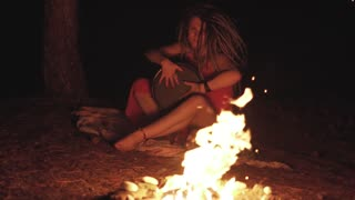 Beautiful young hippie woman with dreadlocks playing on djembe. Funky woman drumming in nature on an ethnic drum with a human skull at night. Slow motion