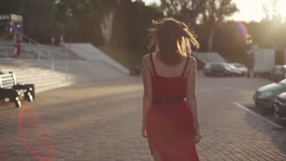 beautiful young red-haired woman walking on street in red dress, having a good time at sunset