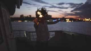 Beautiful young woman dances on the deck of a ship with bengal lights at night. Woman having fun time
