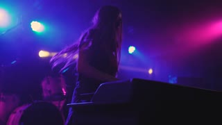 beautiful young woman DJ play the music on the mixing console in the nightclub