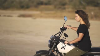 beautiful young woman riding an old cafe racer motorcycle on desert at sunset or sunrise. Female biker. Slow motion