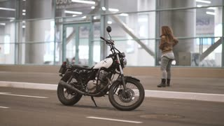 Beautiful young woman riding an old cafe racer motorcycle on street. Female biker at night city.